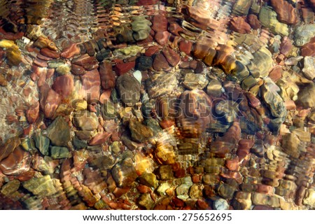 Blurred colored pebbles on the beach with water texture, abstract background. - stock photo