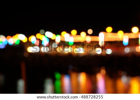 Blurred colorful light abstract background, bokeh multicolor light background in the dark, green blue purple red and yellow lights at night near beach
