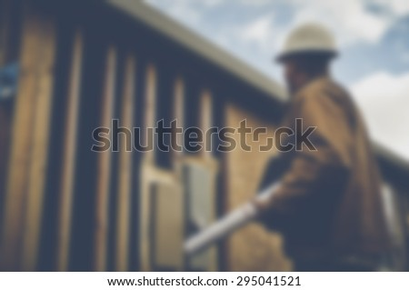 Blurred Construction Inspector Reviewing Construction Site with Instagram Style Filter - stock photo