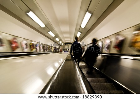 Blurred couple commuting between subway stations - stock photo