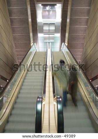 blurred couple on moving escalator - stock photo