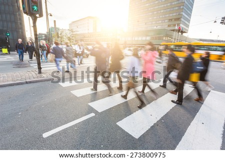 Blurred crowd of people walking on zebra crossing in Copenhagen in late afternoon. Some of them also bring a bike, typical mode of transport in the city. Unrecognizable faces.  - stock photo