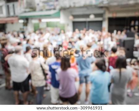 Blurred crowd of people watching a performance on the street in phuket old town