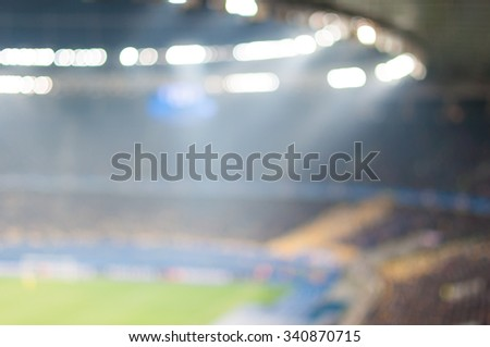 Blurred crowded football stadium with field, stands and spectators. 2016 sport background. - stock photo