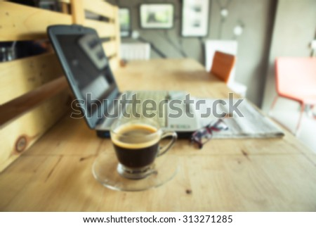 Blurred cup of coffee with newspaper and glasses on table - stock photo