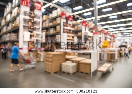Blurred customers shopping in large furniture warehouse with row of aisles and bins from floor to ceiling. Defocused background industrial storehouse interior. Inventory, wholesale, logistic, export