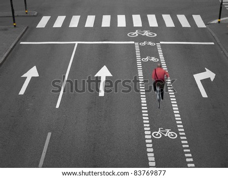 Blurred cyclist on empty street with arrows and a cycling path