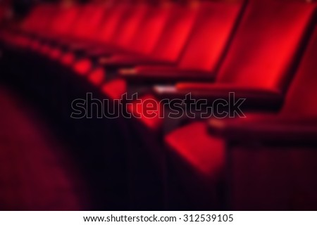 blurred dark background row of empty red theater chairs