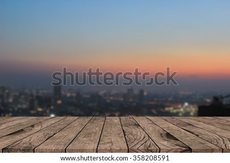 Blurred dark night city background with wood panels perspective.blur downtown skyline backdrop concept.blurry urban sunset/sunrise hours wallpaper with wood tiles stripe floorboard for montage display - stock photo