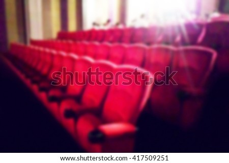 Blurred dark scene background. Cinema and music with audience comfortable red seats and projector. The atmosphere in the theater before the Movies start. - stock photo