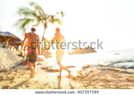 Blurred defocused silhouette of travelers at seaside before sunset - Travel and wanderlust concept with people at Las Cabanas beach by El Nido Palawan - Warm bright filter - Tilted horizon composition - stock photo