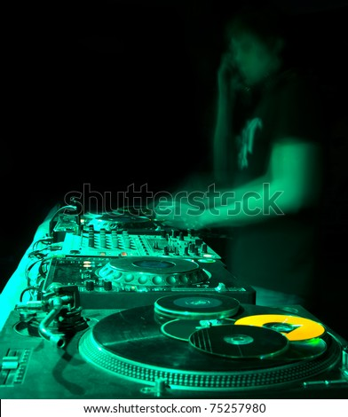 blurred dj at spin table in night club - stock photo