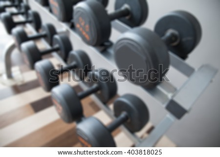 Blurred dumbbells in gym.