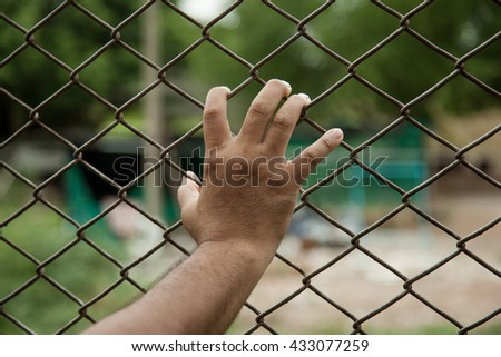 Blurred face and focus in hand of a man in  prison with no freedom concept trying to escape or break out.