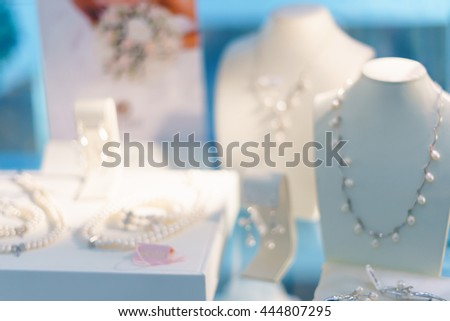 Blurred fashion boutique with jewelry made of precious metals. Store jewelry in silver and gold. Vetrin beautiful jewelry store. Blurred bokeh basic background for design.  - stock photo