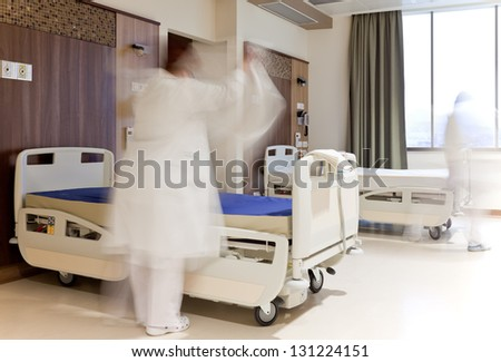 Blurred figure of staff in medical uniform fixing bed in modern hospital room - stock photo
