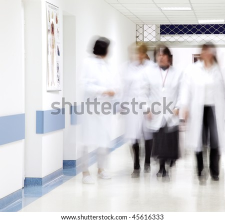blurred figures of doctors and nurses walking in a hospital corridor