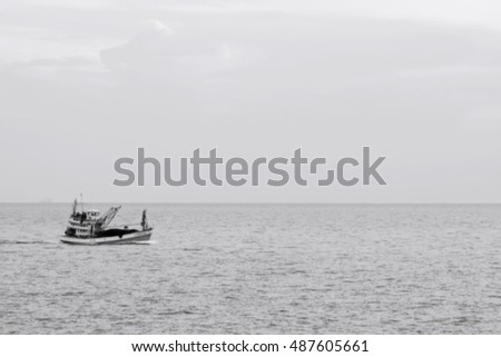 blurred Fishing boat on the sea in rainy day, black and white tone