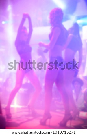 Blurred for background club dance show. Go go dancer. Dance show at night club with lights show. Performance club show during night party.