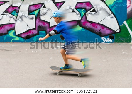 Blurred Full Length Action Shot of Young Boy on Skateboard in front of Graffiti Covered Wall in Urban Skate Park - stock photo