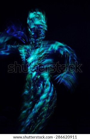 Blurred girl in blue ultraviolet costume on black background - stock photo
