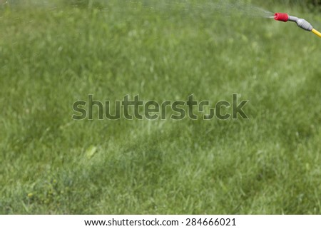 Blurred grass background, sprinkle in the upper right corner and weak rainbow from drops at center. - stock photo