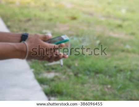 Blurred hand of man Playing smart phone and holding a cigarette.