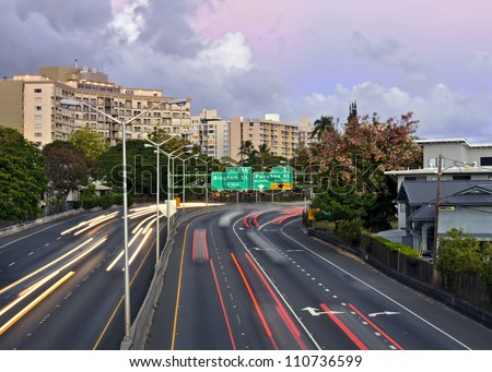 Blurred headlights and taillights of automobiles on the H2 freeway  on Oahu, Hawaii. - stock photo