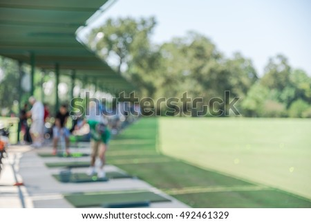 Blurred image a golf driving range practice facility with people swinging, tee-off, putting, hitting range balls. Golf Practice in Driving Range at Houston, Texas, US.Outdoor sport, recreation concept
