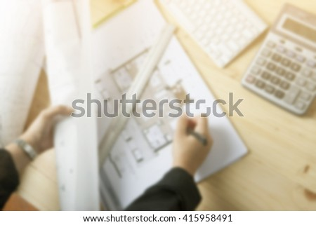 Blurred image and Close-up hand Of female Architect Drawing Blueprint on work space wooden table in offfice ,cross process and soft flare filter  - stock photo