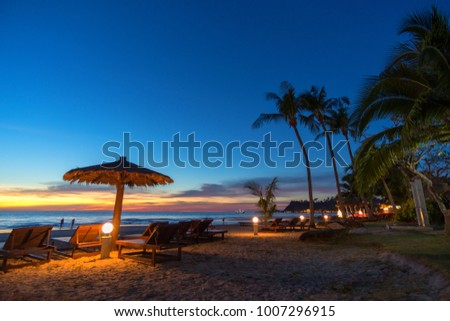 Blurred image. Beach umbrella and sun beds on the sea beach at sunset in thailand. with copy space for your text message