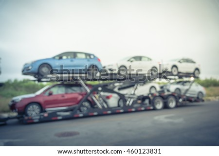 Blurred image big car carrier truck of new cars for batch delivery to dealership. Full load transport truck of new vehicles on country road. Automotive industry abstract background.Vintage filter look