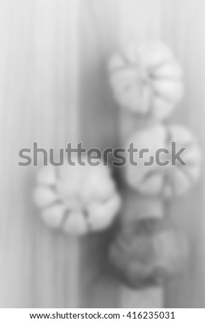 blurred image black and white of artistic onion and garlic on wooden table. for background usage. - stock photo