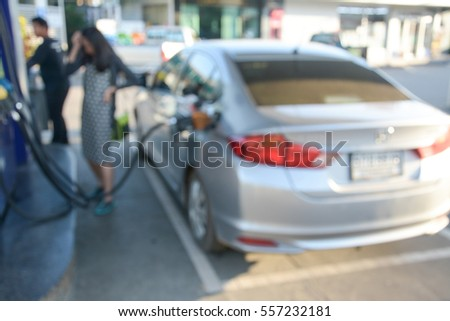 blurred Image holding fuel nozzle and refuel car  in gas station