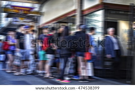Blurred image of a crowd of people lined up on a sidewalk in front of a store.