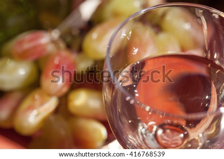 Blurred image of a glass with white wine on the background of the grape. - stock photo