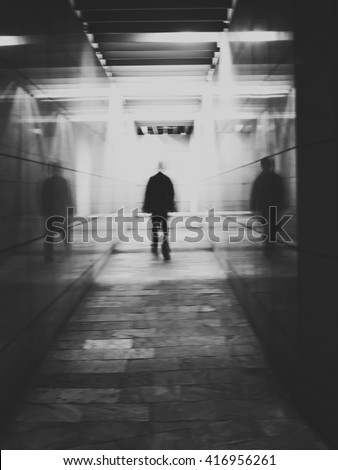 Blurred image of a man walking in an underground passage. Man walking away in a under passage to the light. Black and white image. Motion blur. - stock photo