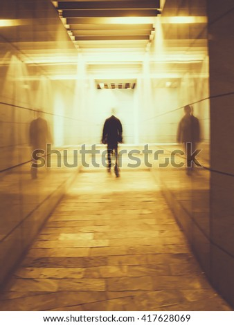 Blurred image of a man walking in an underground passage. Man walking away in a under passage to the light. Toned image. Motion blur. - stock photo