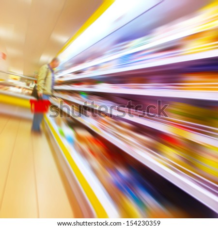 Blurred image of a man with a shopping basket in the grocery store. - stock photo