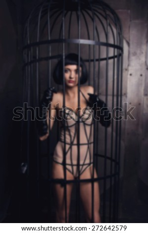 Blurred image of a woman in the background for a steel cage. The woman inside the iron cage. Model is wearing a sexy dress posing in a steel cage.