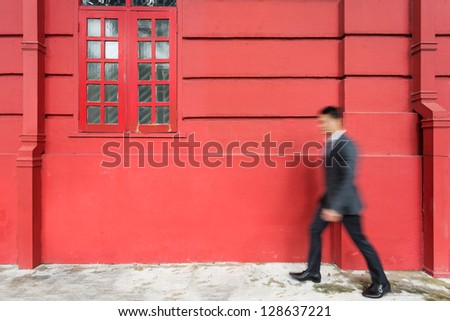 Blurred image of a young Chinese business man.  Busy business person walking past Red Colonial building. - stock photo