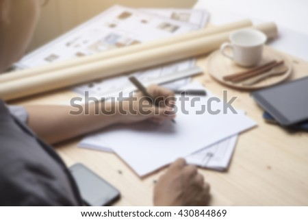 Blurred image of architecture writing blank paper on working table and cross process and soft flare filter
