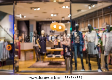 Blurred image of boutique window with dressed mannequins. Boutique display window with mannequins in fashionable dresses.  - stock photo
