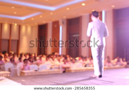 blurred image of businessman giving a speech on the stage - stock photo