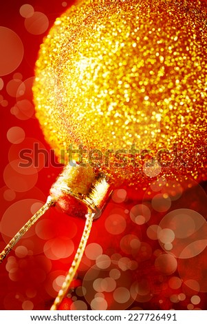 Blurred image of Christmas decoration with gold baubles and glitter on red background. Xmas and new year greeting. Close up, selective focus, bokeh lights. - stock photo