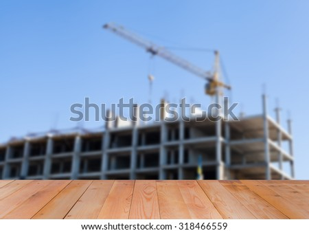 Blurred image of constructing building, wooden background - stock photo
