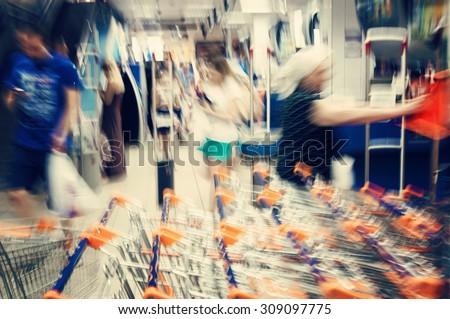 Blurred image of customers and shopping carts in supermarket - stock photo