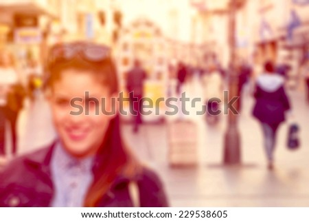 Blurred image of female and people in the city - stock photo