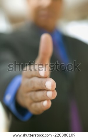 Blurred image of hand shake extended - stock photo