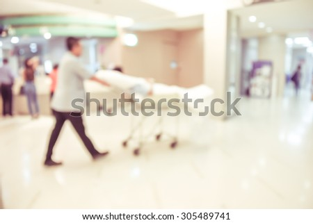 blurred image of modern hospital - patient on stretcher - stock photo